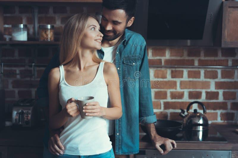 Jong gelukkig paar die en elkaar binnen een nieuwe keuken, geluk in een nieuw huis koesteren bekijken stock foto