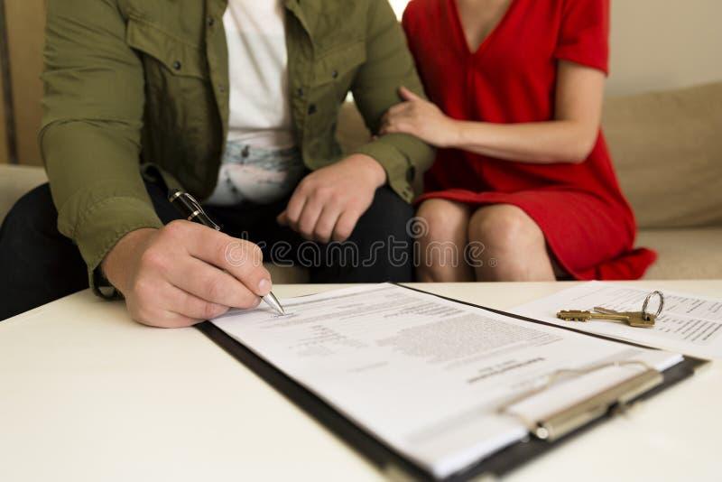 Jong gelukkig paar die het contract van de onroerende goederenaankoop ondertekenen royalty-vrije stock afbeeldingen