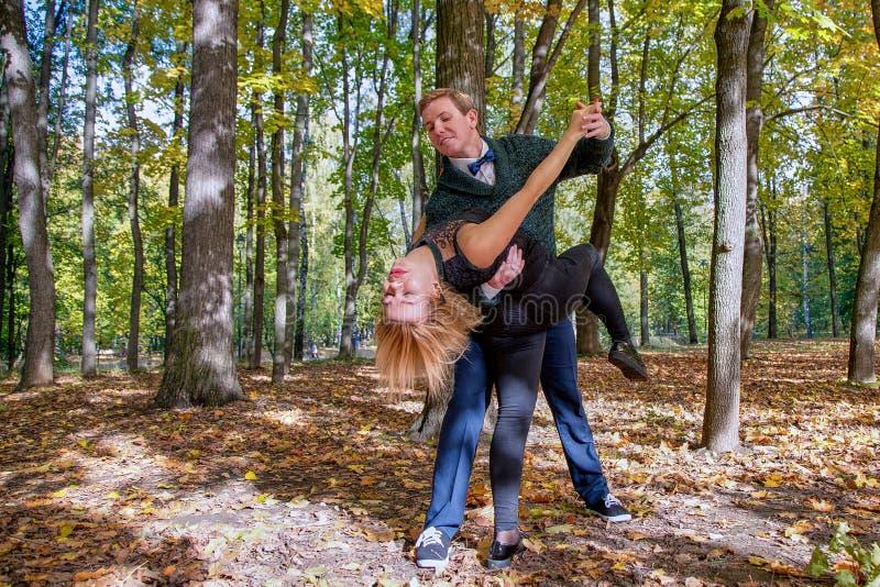 Jong gelukkig paar die in het de herfstpark dansen Zonnige dag, de Gouden herfst royalty-vrije stock foto