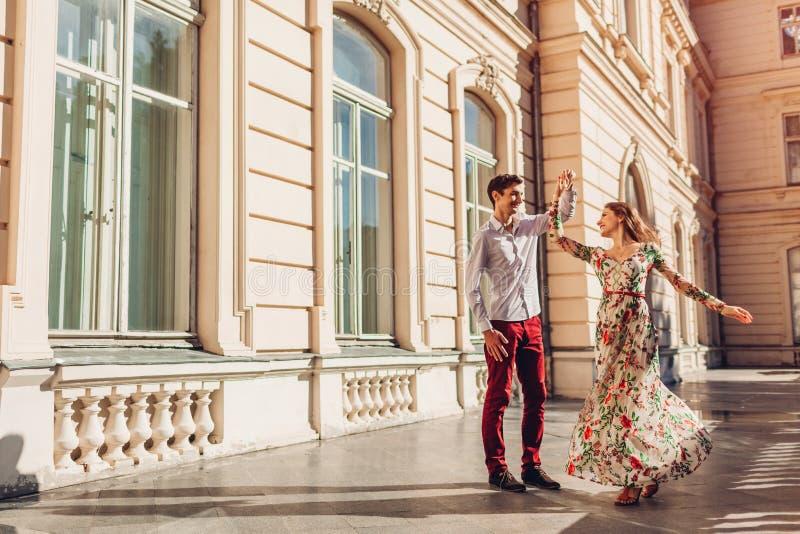 Jong gelukkig paar die in liefde door paleis in openlucht dansen Man en vrouw die pret in stad hebben stock foto's