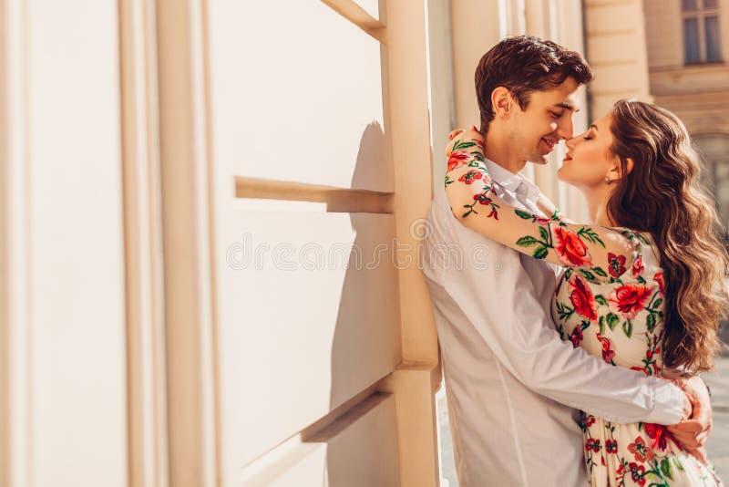 Jong gelukkig paar die in liefde in openlucht koesteren Man en vrouw wat betreft neuzen Romantische datum stock fotografie