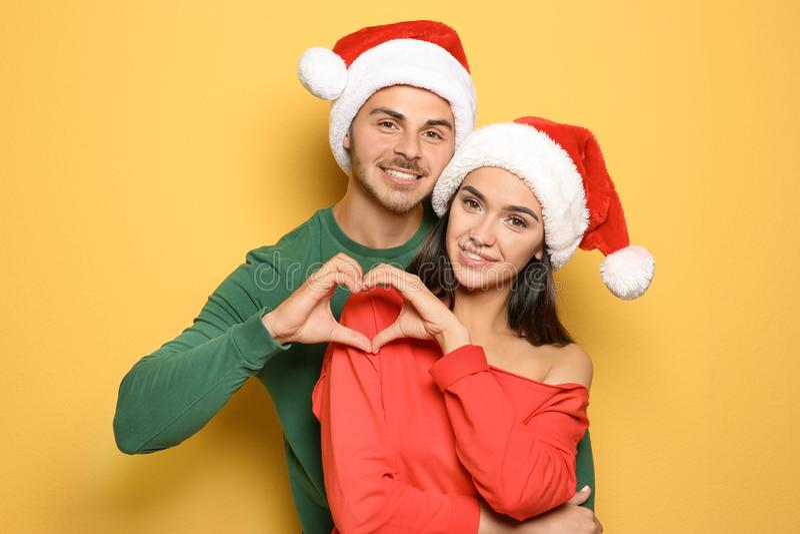 Jong gelukkig paar die met Kerstmanhoeden handen zetten stock foto's
