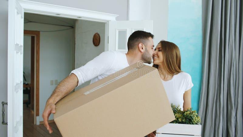 Jong gelukkig paar die in nieuw huis na het bewegen van dag en kus lopen elkaar royalty-vrije stock afbeeldingen