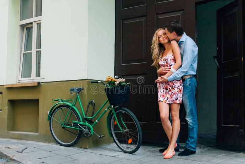 Jong gelukkig paar die op de straat dichtbij fiets koesteren stock afbeelding
