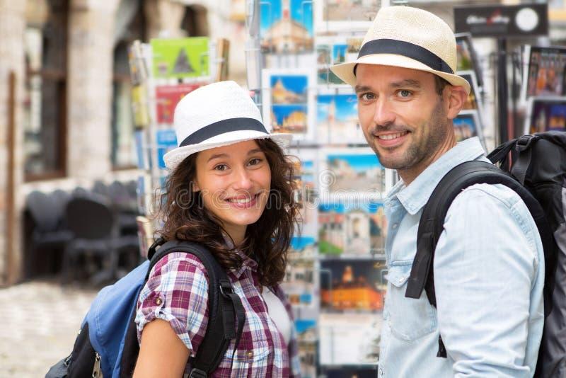 Jong gelukkig paar die prentbriefkaaren kiezen tijdens vakantie royalty-vrije stock afbeelding