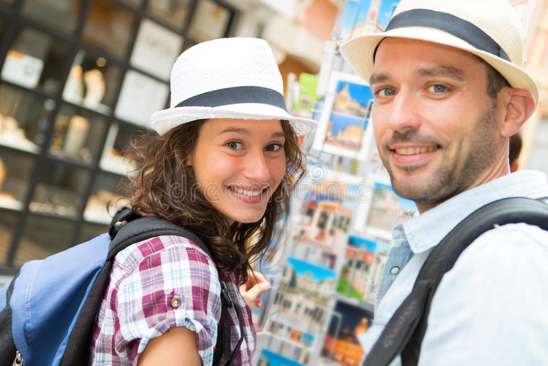 Jong gelukkig paar die prentbriefkaaren kiezen tijdens vakantie stock foto