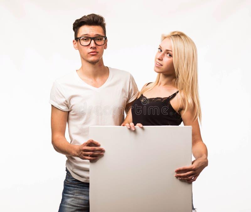 Jong gelukkig paar die presentatie tonen die aanplakbiljet richten royalty-vrije stock afbeelding