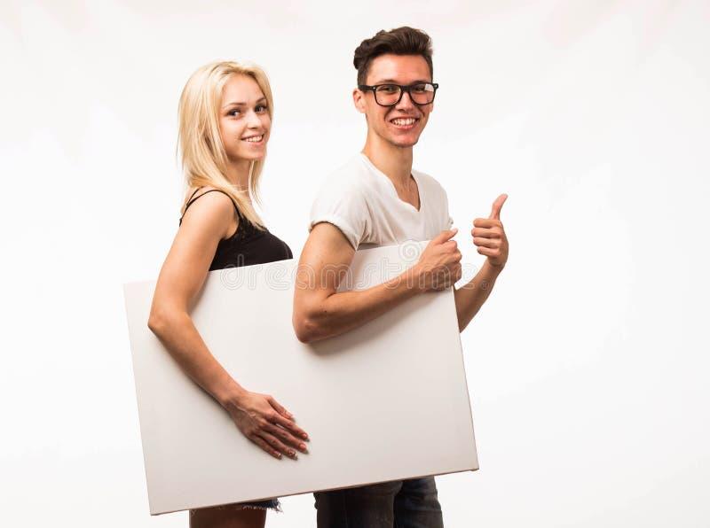 Jong gelukkig paar die presentatie tonen die aanplakbiljet richten stock afbeeldingen