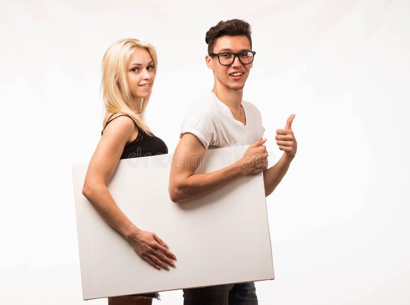 Jong gelukkig paar die presentatie tonen die aanplakbiljet richten royalty-vrije stock foto's
