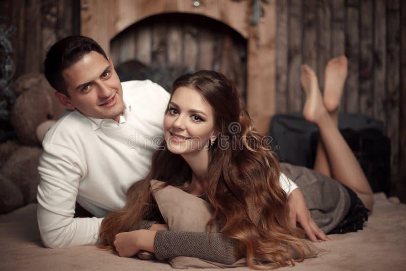 Jong gelukkig paar in liefde die op deken in comfortabel houten binnenland liggen royalty-vrije stock foto's