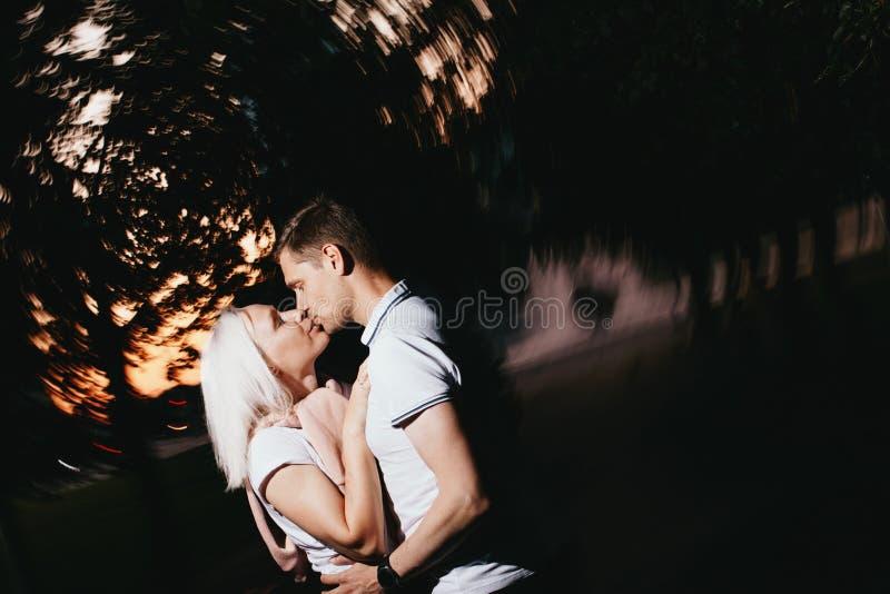 Jong gelukkig paar in liefde het kussen in nachtpark Foto met flitsgevolgen stock afbeelding