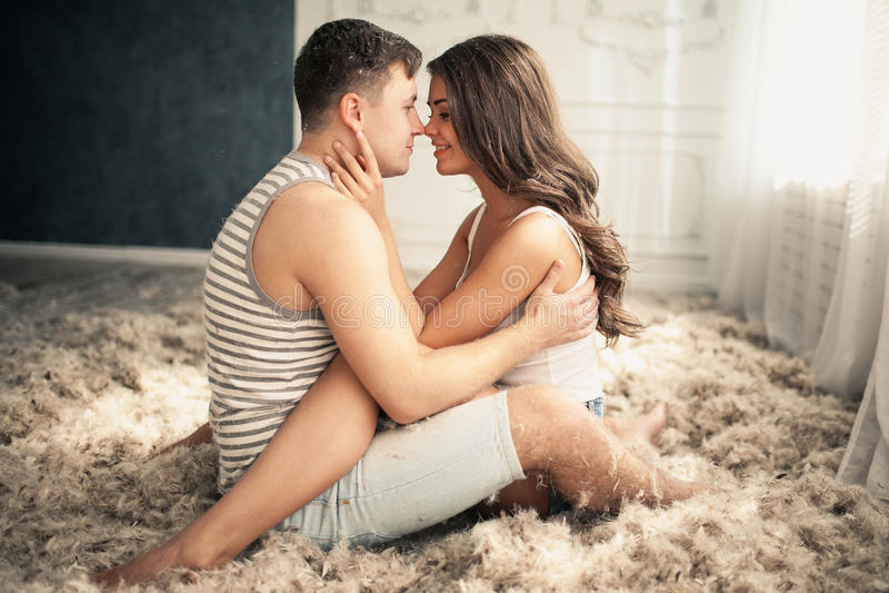 Jong Gelukkig Paar in Liefde Vele veren op de vloer stock foto's