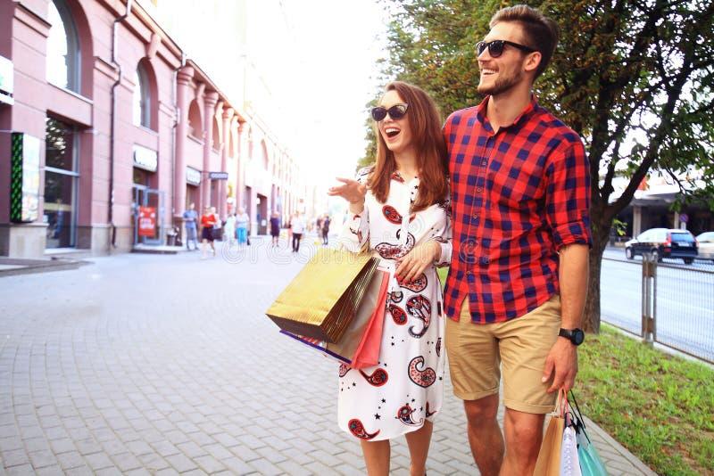 Jong gelukkig paar met het winkelen zakken in de stad stock fotografie