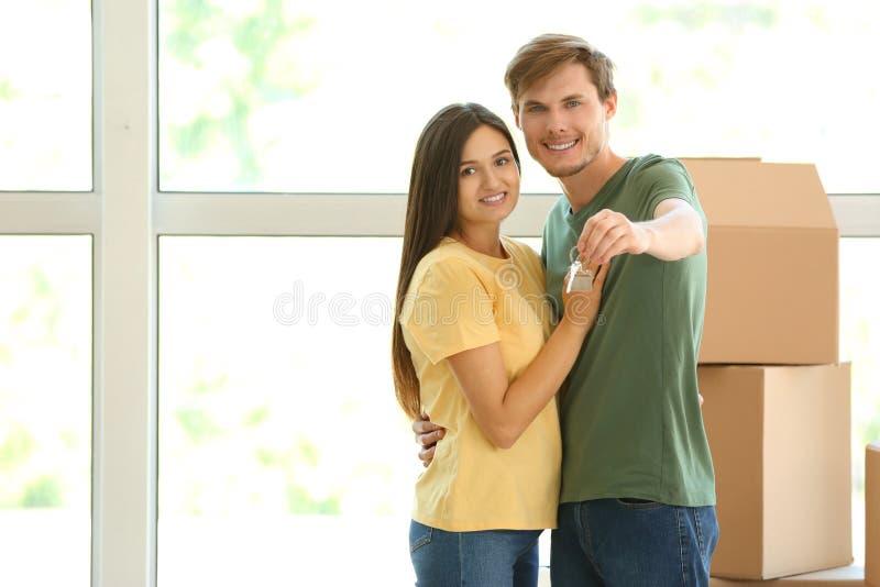 Jong gelukkig paar met sleutel van hun nieuw huis en bewegende dozen binnen stock afbeelding
