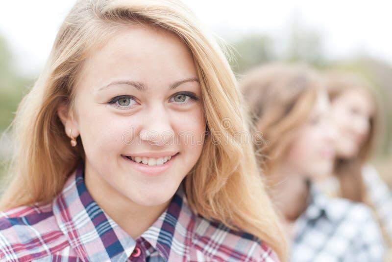 Jong gelukkig tienermeisje met vrienden stock foto