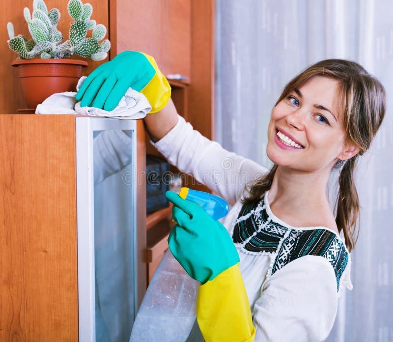 Jong gelukkig volwassen brunette die met reinigingsmiddel bestrooien stock afbeelding