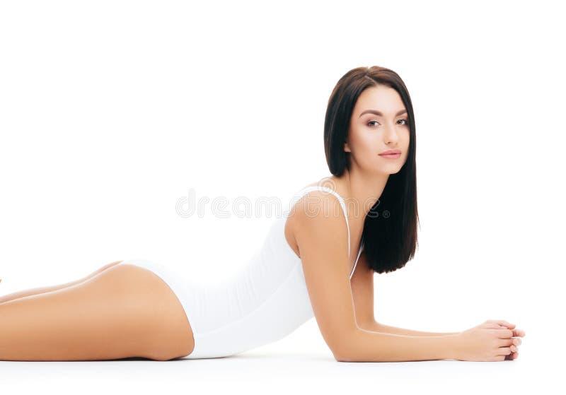 Jong, geschikt en mooi donkerbruin meisje in wit zwempak stock fotografie