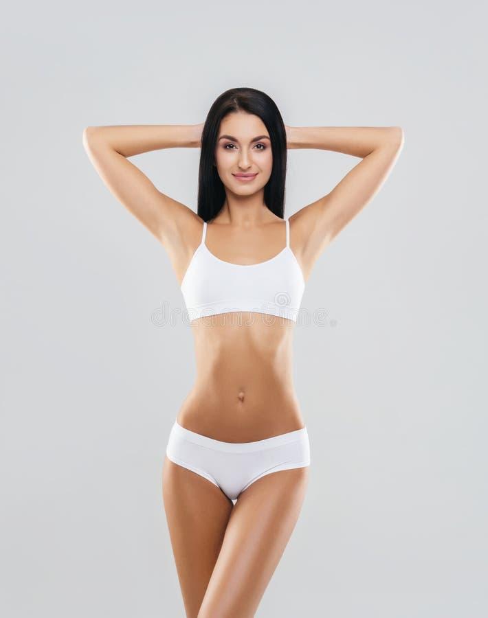 Jong, geschikt en mooi donkerbruin meisje in wit zwempak royalty-vrije stock fotografie