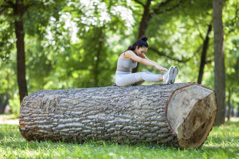 Jong geschikt mooi meisje die en zich op een boomlogboek rusten uitrekken royalty-vrije stock foto