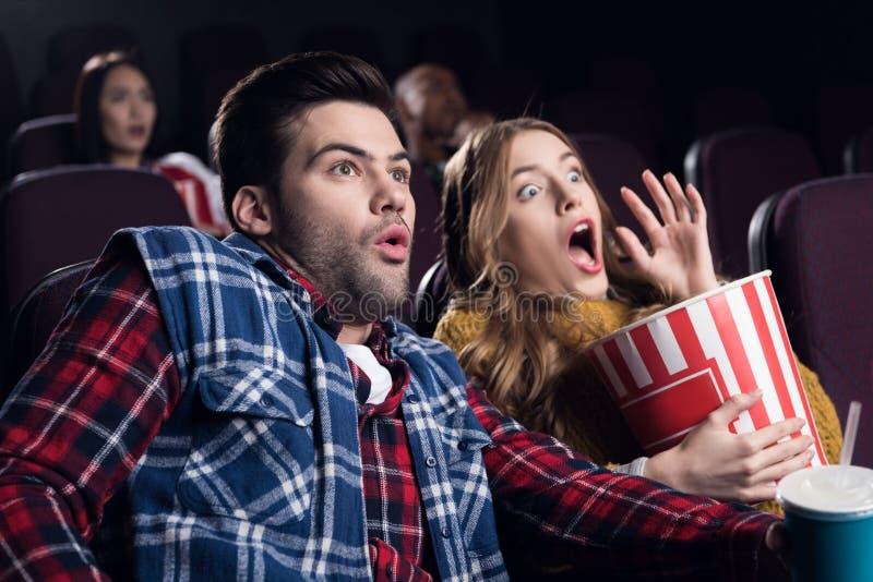 jong geschokt paar met popcorn het letten op film stock foto's