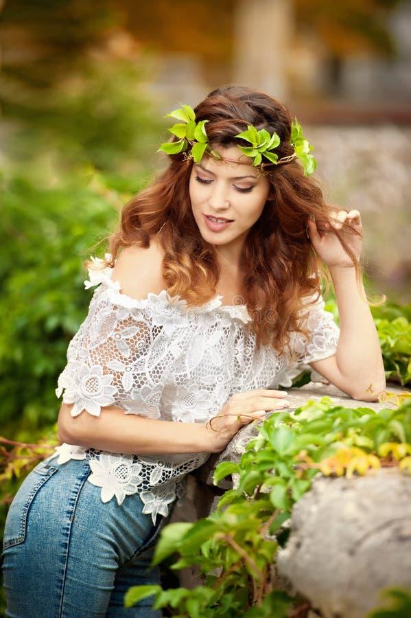Jong geschoten meisje met kroon van groene bladeren, in openlucht Portret van mooie vrouw met lang haar en lave witte blouse royalty-vrije stock foto