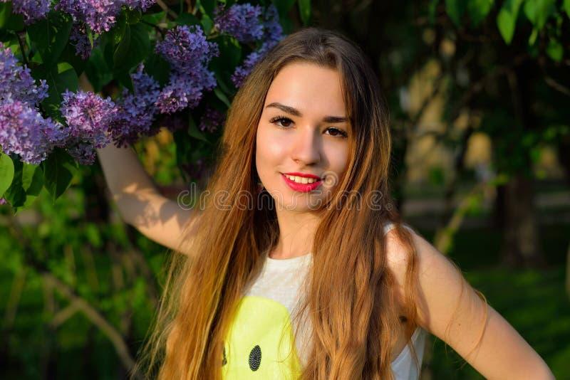 Jong glimlachend meisje dichtbij bloeiend lilac Bush royalty-vrije stock foto's