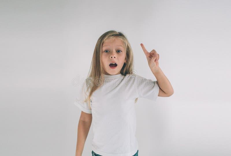 Jong glimlachend meisje die een goed idee hebben Portret van een opgewekt kind die in witte T-shirt vinger benadrukken op copyspa stock afbeelding