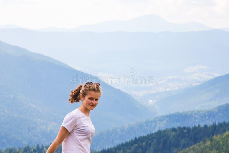 Jong glimlachend meisje die op bergenachtergrond happy_ voelen royalty-vrije stock fotografie