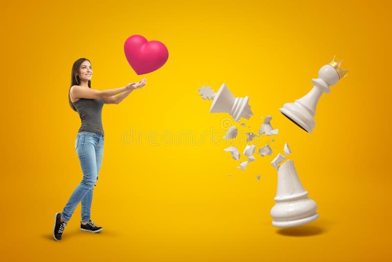 Jong glimlachend meisje die in vrijetijdskleding groot rood hart houden, die zich naast groot wit pand bevinden die gouden kroon  stock afbeeldingen