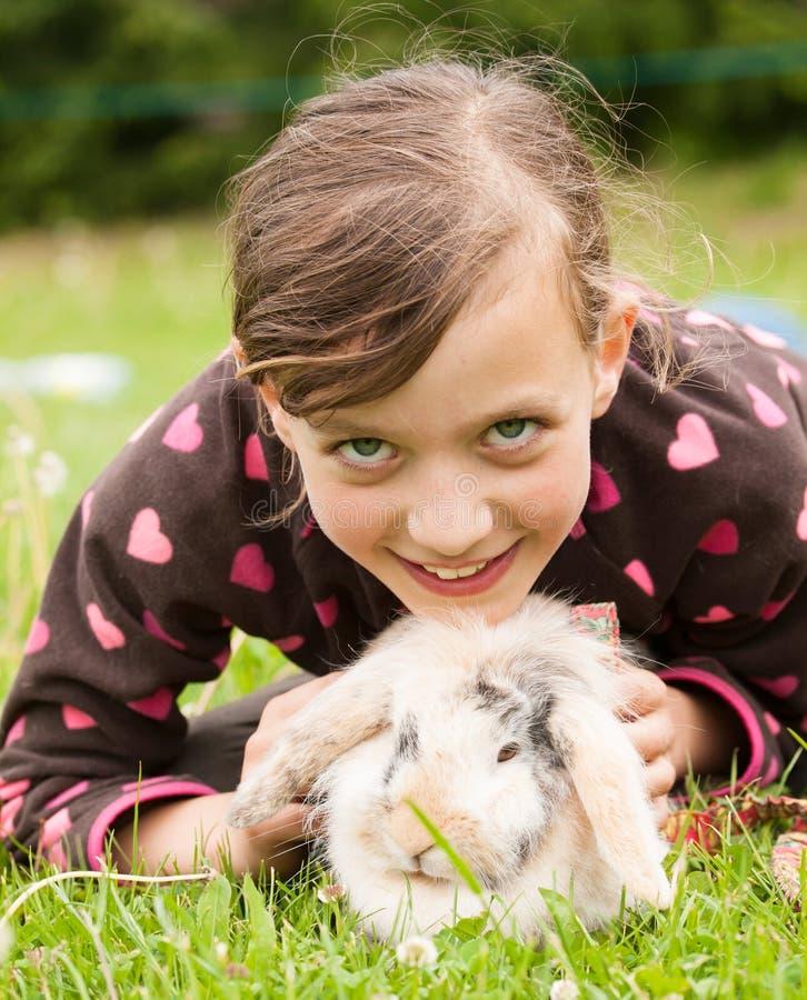 Jong glimlachend meisje met haar konijnhuisdier royalty-vrije stock afbeeldingen