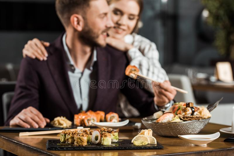 jong glimlachend paar die diner hebben en heerlijke sushibroodjes eten stock afbeelding