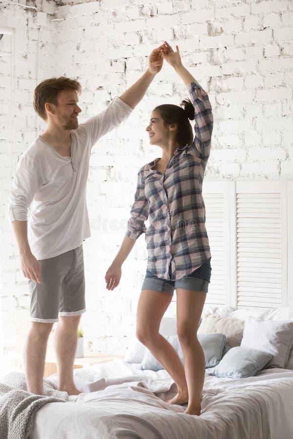 Jong glimlachend paar die in liefde bij bed samen in slaapkamer dansen stock foto's