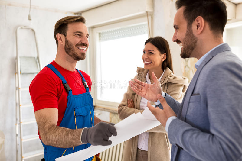 Jong glimlachend paar en bouwersmanusje van alles die over details spreken stock foto