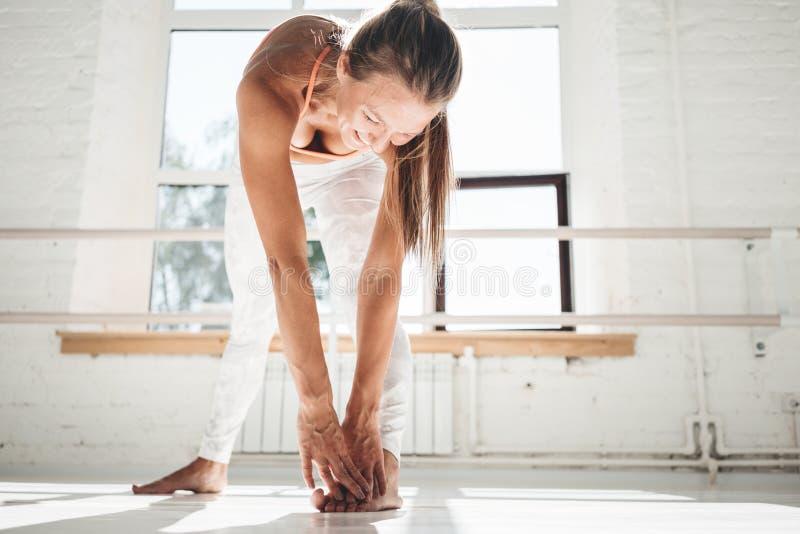 Jong glimlachend wijfje die de uitrekkende binnen witte gymnastiek van het oefeningenbeen doen royalty-vrije stock afbeeldingen