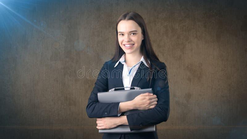 Jong het glimlachen onderneemsterportret met grijze aktentas, donkere achtergrond stock foto's