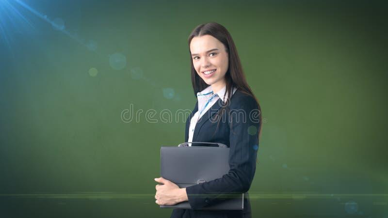Jong het glimlachen onderneemsterportret met grijze aktentas, donkere achtergrond royalty-vrije stock afbeeldingen