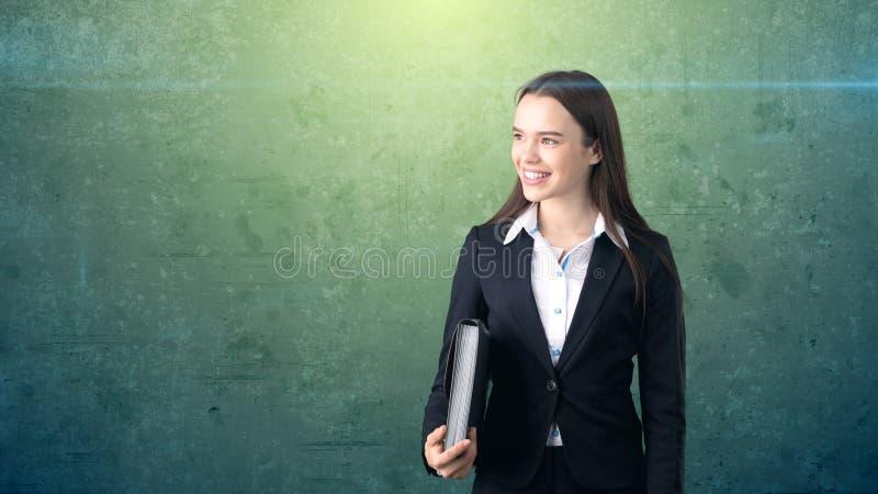 Jong het glimlachen onderneemsterportret met grijze aktentas, donkere achtergrond royalty-vrije stock fotografie