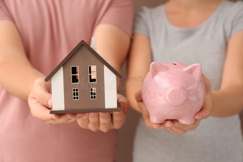 Jong het huismodel van de paarholding en spaarvarken, close-up Het concept van de hypotheek stock foto