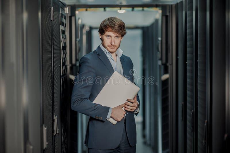 Jong het ingenieurs bedrijfsmens met dunne moderne aluminiumlaptop in de ruimte van de netwerkserver royalty-vrije stock foto