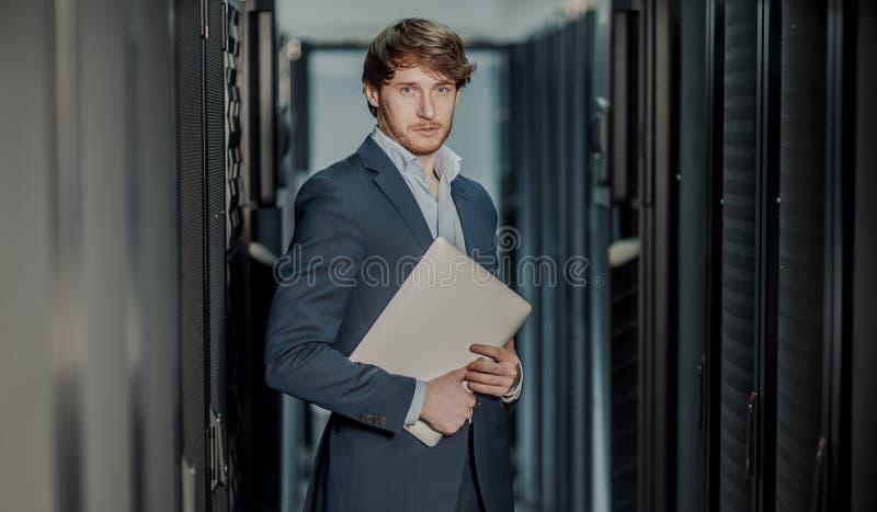 Jong het ingenieurs bedrijfsmens met dunne moderne aluminiumlaptop in de ruimte van de netwerkserver stock foto