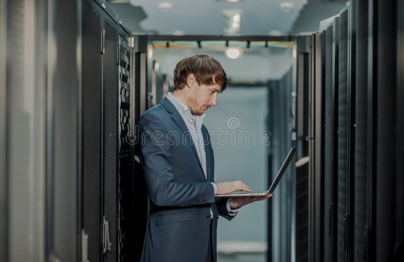 Jong het ingenieurs bedrijfsmens met dunne moderne aluminiumlaptop in de ruimte van de netwerkserver royalty-vrije stock afbeelding
