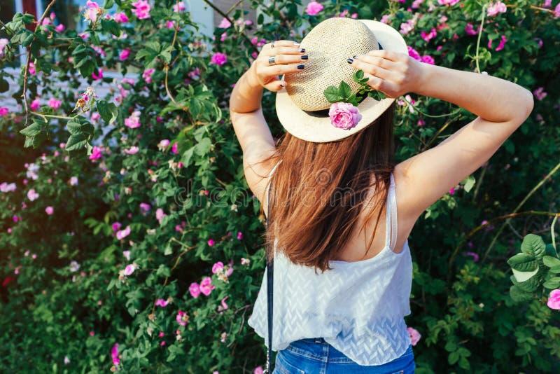 Jong hipstermeisje die hoed dragen die door bloeiende rozen lopen De vrouw geniet van bloemen in park De zomeruitrusting stock afbeeldingen