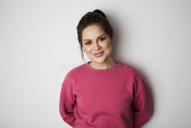 Jong hipstermeisje die roze hoody met ruimte voor uw embleem of ontwerp dragen Model van roze hoody op witte lege muur binnen royalty-vrije stock foto's