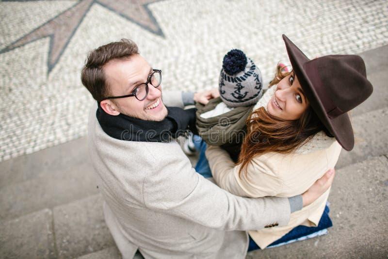 Jong hipsterpaar met baby die oude stadsstraten lopen stock foto