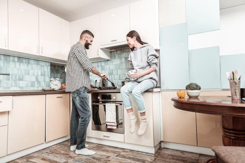 Jong houdend van paar die heerlijk diner samen koken stock afbeelding
