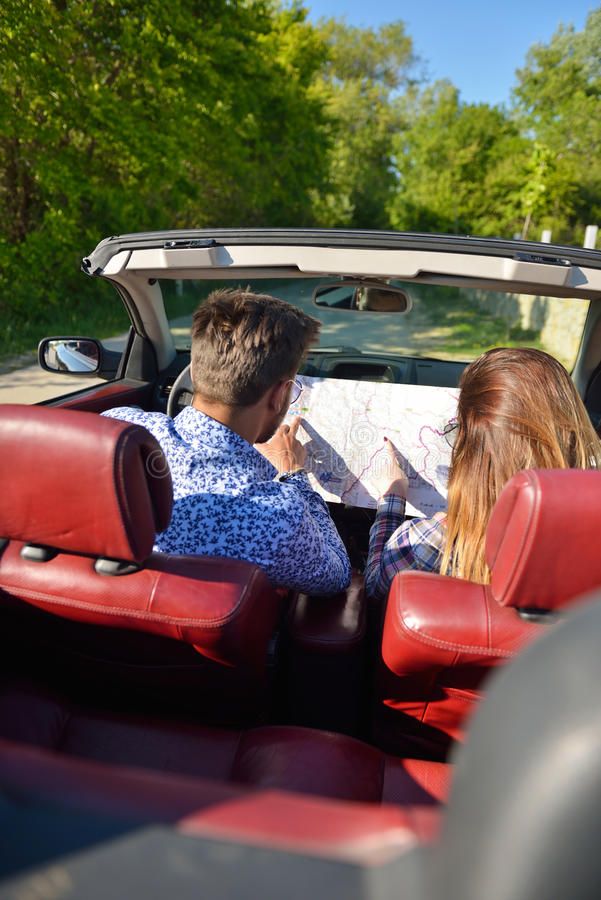 Jong houdend van paar die hun romantisch avontuur plannen Blij jong paar die terwijl het berijden in hun convertibel glimlachen royalty-vrije stock foto
