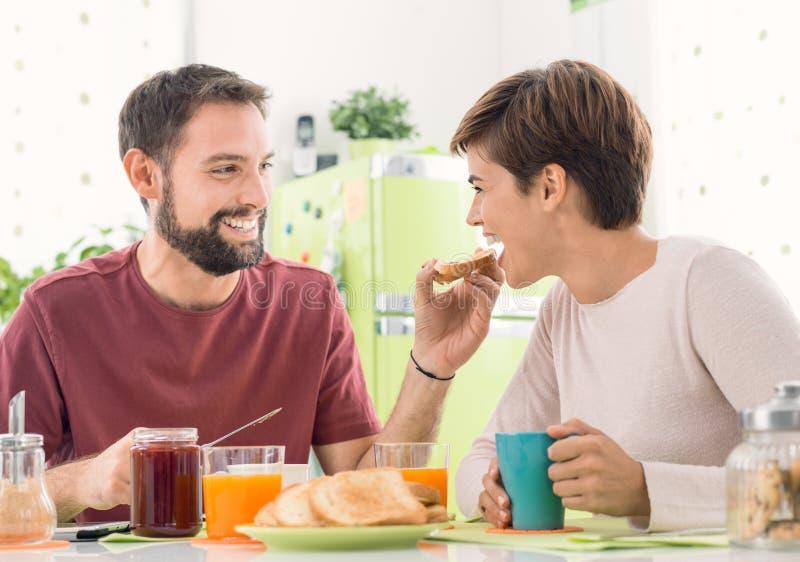 Jong houdend van paar die ontbijt hebben thuis stock afbeelding