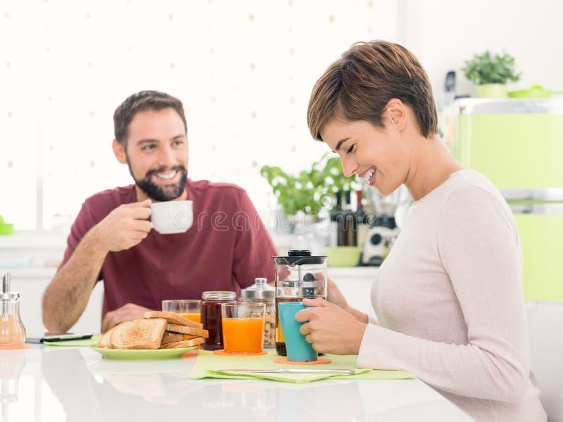 Jong houdend van paar die ontbijt hebben thuis stock foto's