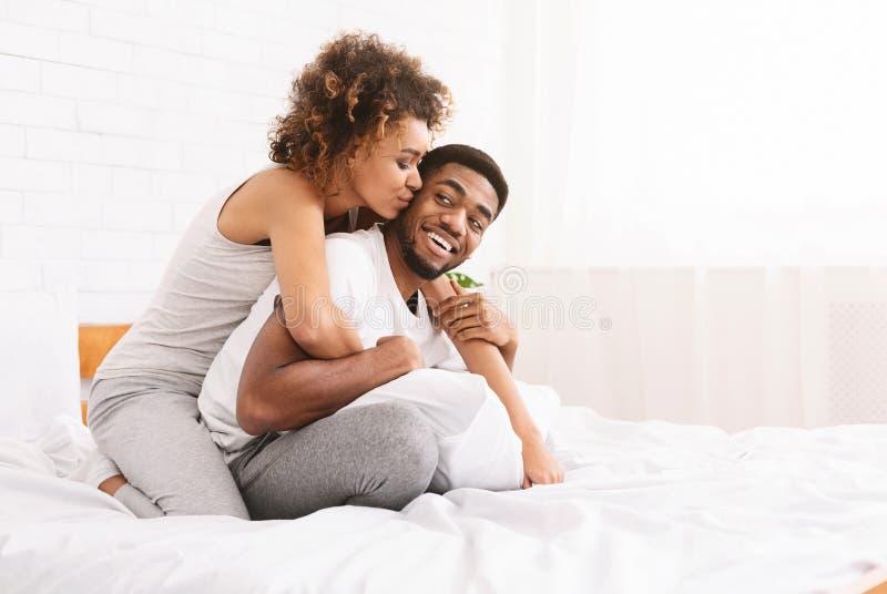 Jong houdend van paar die romantische tijden in slaapkamer hebben royalty-vrije stock foto