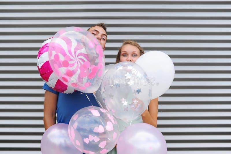 Jong houdend van paar die zich over gestreepte muur met heel wat kleurrijke ballons bevinden stock foto's